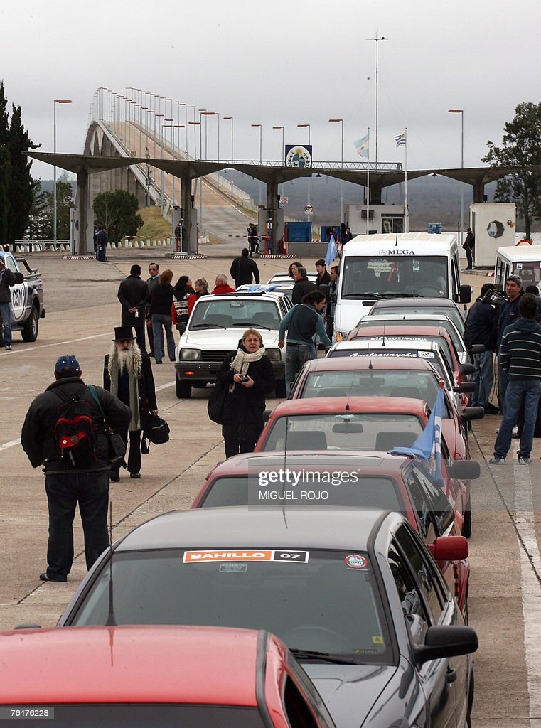 Argentinian activists wait outside their cars to go through the Customs procedures after crossing the Gen. San Martin international bridge in the Uruguay-Argentina border, near the city of Fray Bentos, 350 km northwest of Montevideo, 02 September, 2007. Argentinian environmentalists are crossing the border Sunday to demonstrate against the construction of a Finnish pulp mill on the banks of the Uruguay river, in the Uruguayan side, as they believe it will pollute the bordering river. AFP PHOTO/Miguel ROJO