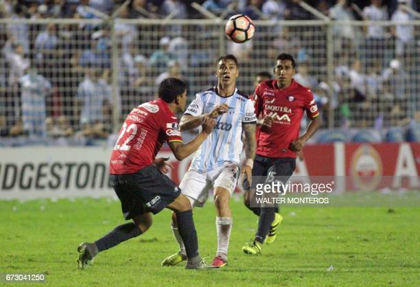 Argentinian Atletico Tucuman player Fernando Zampedri vies for the ball with Edward Zenteno and Cristhian Machado of Bolivian Wilstermann during...