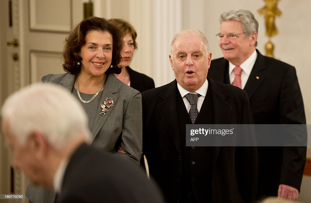 Argentinian- born conductor Daniel Barenboim (2nd,R) reacts seeing Former German President Richard von Weizaecker (L) as he walks in with his wife Elena Bashkirova (2nd,L) and German President Joachim Gauck (R) to be presented with the German order of Merit for services to music and culture before a dinner in his honour at the Bellevue Palace in Berlin on February 5, 2013.