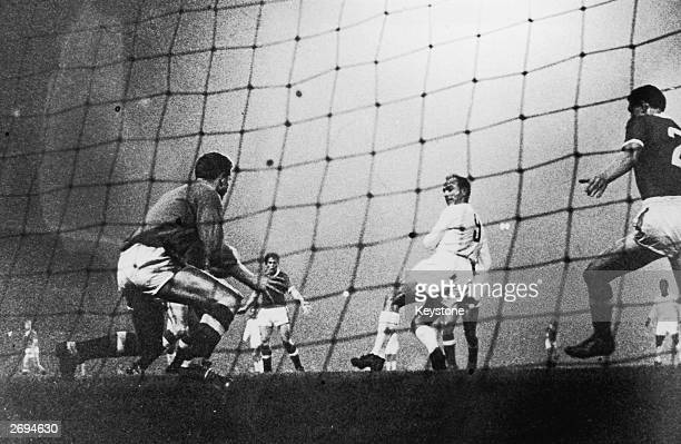 Argentinian born Real Madrid centre forward Alfredo Di Stefano back heels the ball past the Manchester United goalkeeper Harry Gregg at Old Trafford