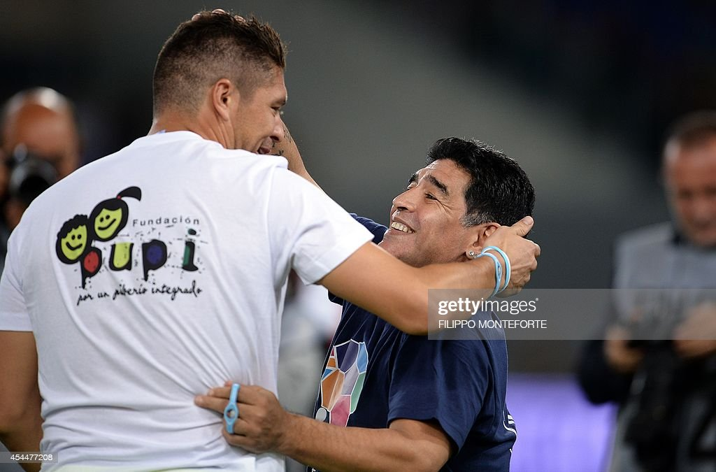 Argentinian Diego Armando Maradona (R) hugs goalkeeper Juan Pablo Carrizo as he arrives to play the inter religious 'match for peace' football game, in Rome's Olympic Stadium on September 1, 2014. AFP PHOTO/Filippo MONTEFORTE