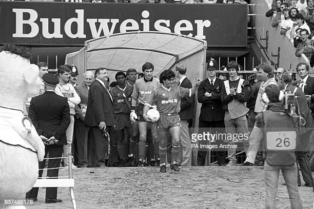 Argentinian Diego Maradona is all smiles as he leads out the Rest of the World XI at Wembley Stadium months after his 'Hand of God' knocked England...