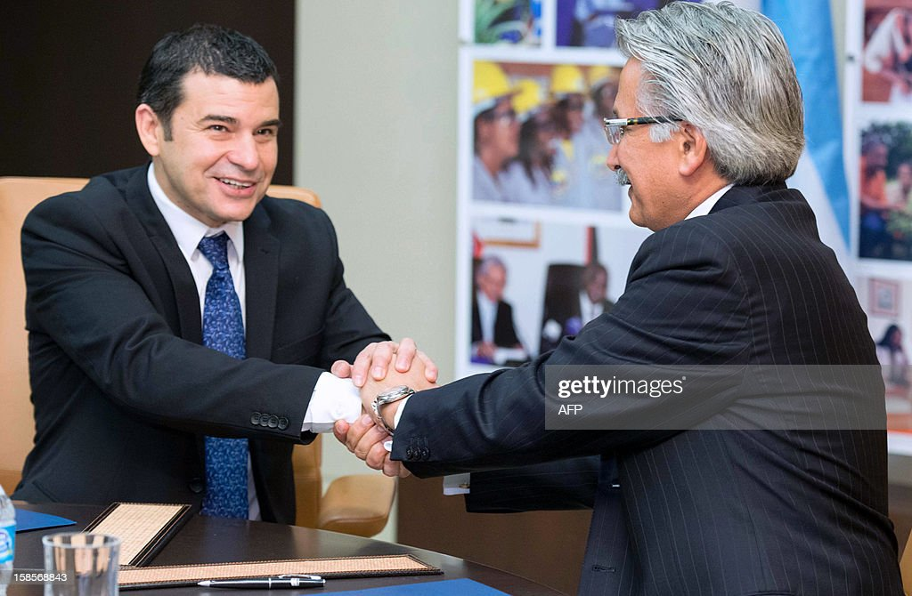 Argentinian energy company YPF's CEO, Miguel Galuccio (L), and US energy corporation Chevron's CEO for Latin America and Africa, Ali Moshiri, shake hands after signing an agreement on December 19, 2012 in Houston, Texas, USA, to start non-conventional oil exploitation in Neuquen, Argentina.
