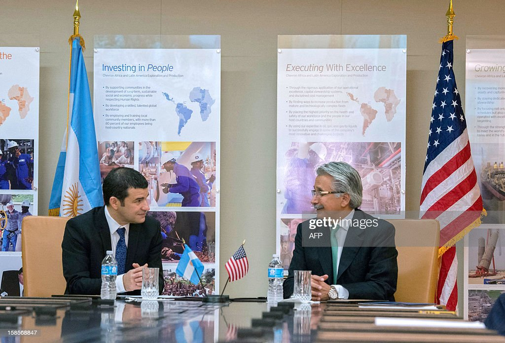 Argentinian energy company YPF's CEO, Miguel Galuccio (L), and US energy corporation Chevron's CEO for Latin America and Africa, Ali Moshiri, speak during the signing of an agreement on December 19, 2012 in Houston, Texas, USA, to start non-conventional oil exploitation in Neuquen, Argentina.