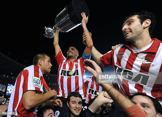 Argentinian Estudiantes de La Plata's team captain Juan Sebastian Veron holds up the trophy next to his teammates after winning the Libertadores Cup...