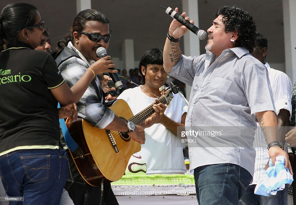 Argentinian football icon and former player Diego Maradona (R) performs onstage with local musicians during an appearance at a stadium in Kannur, India's Kerala state, on October 24, 2012. Maradona is on a private visit to the southern Indian state of Kerala, his second visit to the country following a trip to Kolkata in 2008. AFP PHOTO/STR