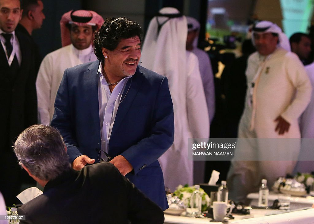 Argentinian football icon and former player Diego Maradona (front-L) smiles before attending a panel discussion during the first session of the International Sports Conference in Dubai on December 28, 2012.