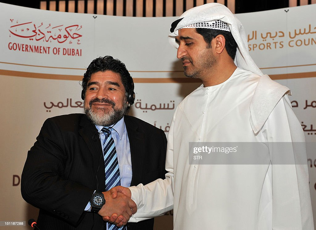 Argentinian football legend Diego Maradona (L) shakes hands with Ahmed al-Sharif, secretary general of Dubai Sports Council (DSC), during a press conference in the Gulf emirate of Dubai late on September 2, 2012 to announce that Maradona has been appointed as Honorary Ambassador of Sports in Dubai. AFP PHOTO/STR