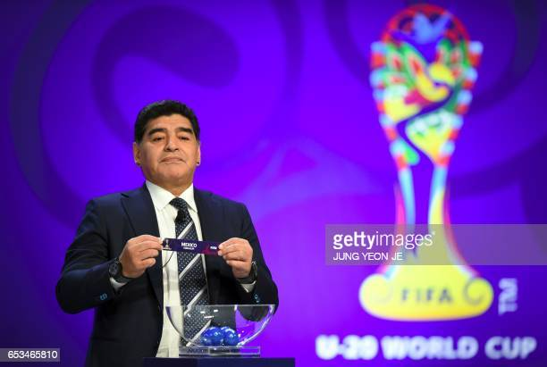 Argentinian football star Diego Maradona holds up the name of Mexico during the official draw for the FIFA under20 football World Cup in Suwon south...