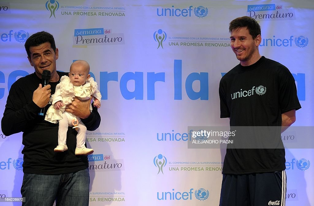 Argentinian football star player and UNICEF Goodwill Ambassador Lionel Messi (R) smiles as the ceremony presenter holds Azul Urrutia -- a baby born prematurely -- during the launching of the 'Week of Premature Birth' campaign, in Ezeiza, Buenos Aires on March 21, 2013. Eight percent of the babies in Argentina are born before the term, which is the leading cause of infant mortality during the first year. AFP PHOTO / Alejandro PAGNI