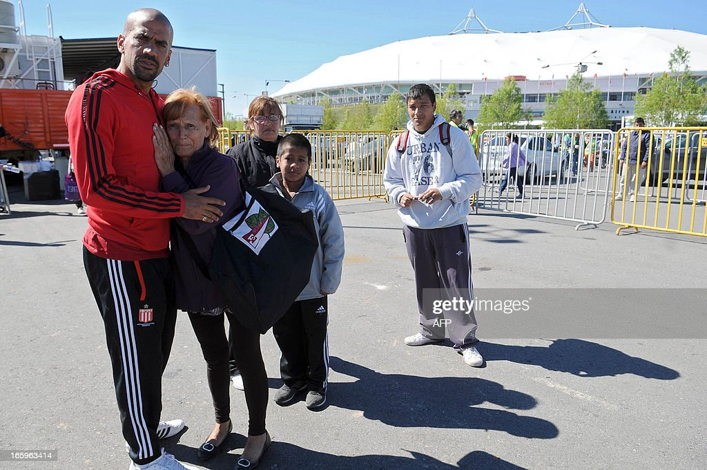 Argentinian former football player and director of Estudiantes de La Plata team, Juan Sebastian Veron (L), poses with a woman as he takes part in the handling of food for those affected by the floods at the Unico stadium in La Plata, Argentina on April 7, 2013.