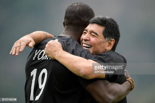 Argentinian former soccer star Diego Maradona is congratiulated by Trinidad former football player Dwight Yorke during 'The Gianni's game the match...