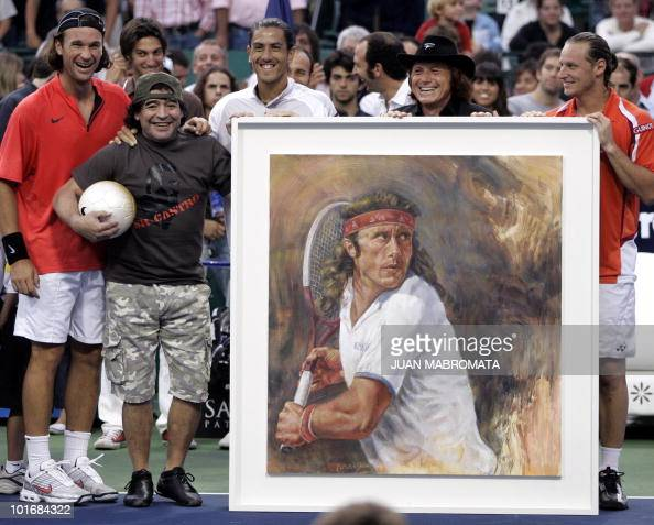 Argentinian former tennis player Guillermo Vilas receives the present of a painting from Argentina' s Tennis Cup 2006 in company of Argentinian...