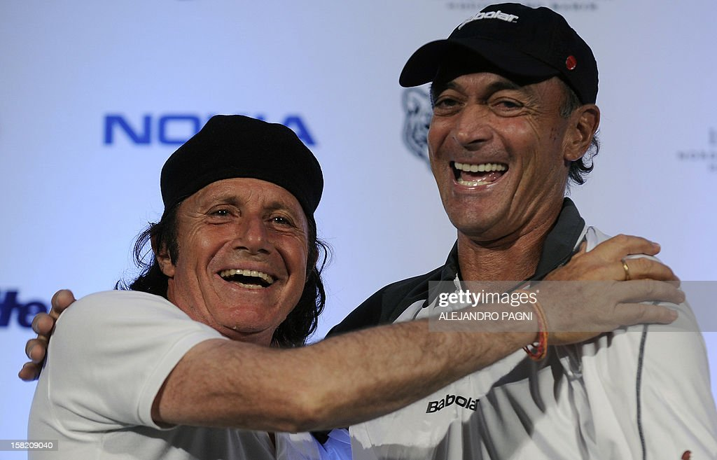 Argentinian former tennis players Guillermo Vilas (L) and Jose Luis Clerc hug during their press conference, in Tigre, near Buenos Aires, on December 11, 2012. Vilas and Clerc will play before two exhibition matches between Argentinian Juan Martin Del Potro and Swiss tennis player Roger Federer next 12 and 13 December. AFP PHOTO / Alejandro PAGNI