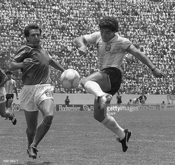 Argentinian forward Diego Maradona kicks the ball past Italian defender Gaetano Scirea to tie the score at 1 during the World Cup first round soccer...