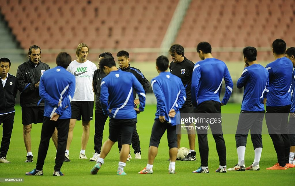 Argentinian head coach Sergio Batista (2nd-L) talks to his Shanghai Shenhua before a training session at Hongkou stadium in Shanghai on October 19, 2012. Football star Didier Drogba has injured his right ankle so he will not play the next match for his Chinese club after returning from international duty and into a row that has seen his teammates reportedly refusing to practise over unpaid wages. AFP PHOTO/Peter PARKS