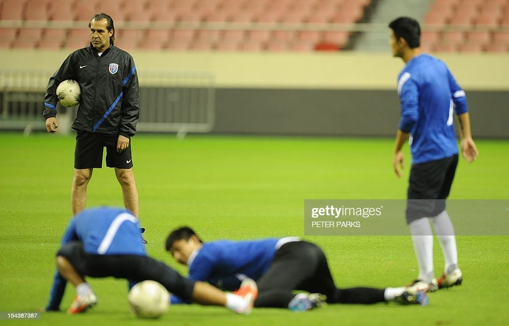 Argentinian head coach Sergio Batista (L) watches as his Shanghai Shenhua team warms up before a training session at Hongkou stadium in Shanghai on October 19, 2012. Football star Didier Drogba has injured his right ankle so he will not play the next match for his Chinese club after returning from international duty and into a row that has seen his teammates reportedly refusing to practise over unpaid wages. AFP PHOTO/Peter PARKS