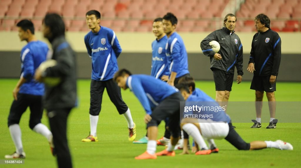 Argentinian head coach Sergio Batista (2nd-R) watches as his Shanghai Shenhua team warms up before a training session at Hongkou stadium in Shanghai on October 19, 2012. Football star Didier Drogba has injured his right ankle so he will not play the next match for his Chinese club after returning from international duty and into a row that has seen his teammates reportedly refusing to practise over unpaid wages. AFP PHOTO/Peter PARKS