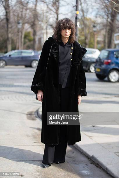 Argentinian model Mica Arganaraz wears an all black outfit with a large black coat and militarystyle asymmetrical black jacket with buttons and...