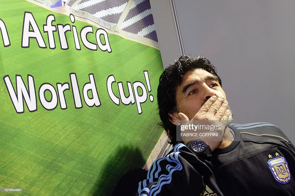 Argentinian national football team coach Diego Maradona gestures close to a poster upon his arrival with his squad at the O. R. Tambo international airport on May 29, 2010 in Johannesburg ahead of the 2010 FIFA World Cup in South Africa. Argentina will play their first match against Nigeria on June 12.