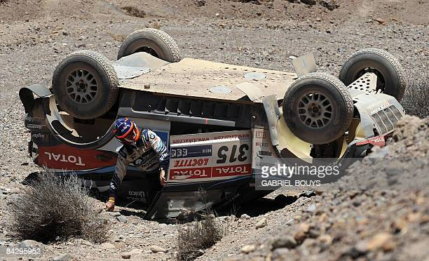 Argentinian Orlando Terranova's codriver Alain Guehennec of France gets out after the crash of his BMW from the top of the hill during the 10th stage...