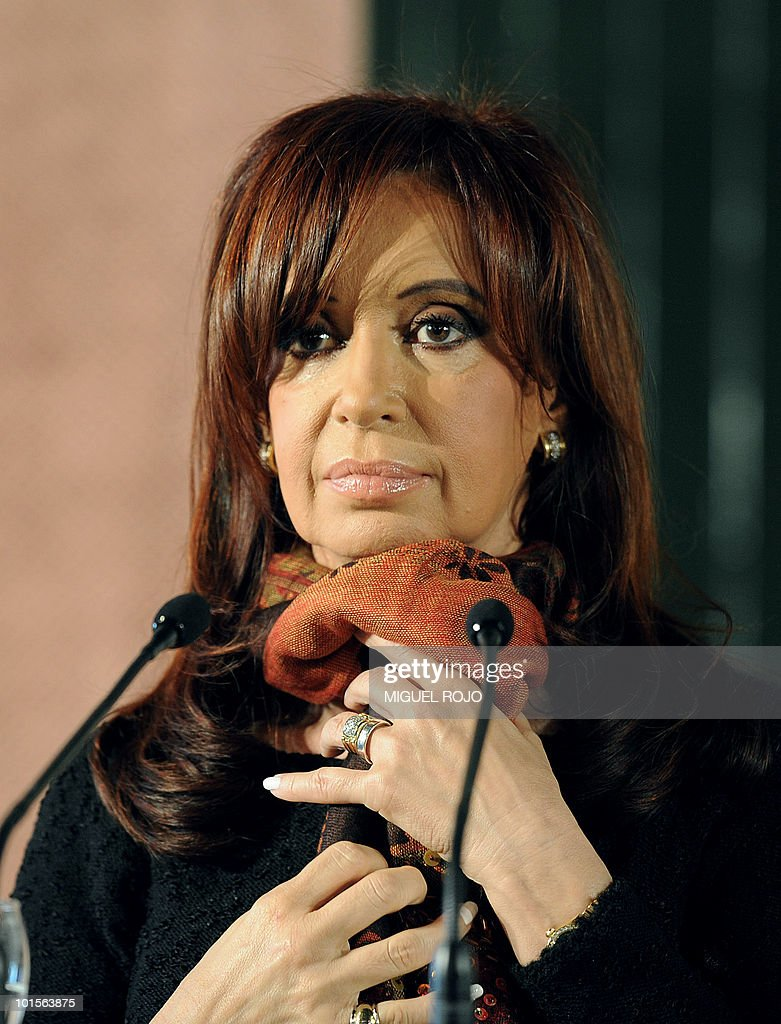 Argentinian President Cristina Fernandez de Kirchner straightens her shawl during a press conference, after a meeting with her Uruguayan counterpart Jose Mujica (not in frame), at the Anchorena presidential residence, in Colonia, 180 km west of Montevideo, on June 2, 2010. AFP PHOTO/Miguel ROJO