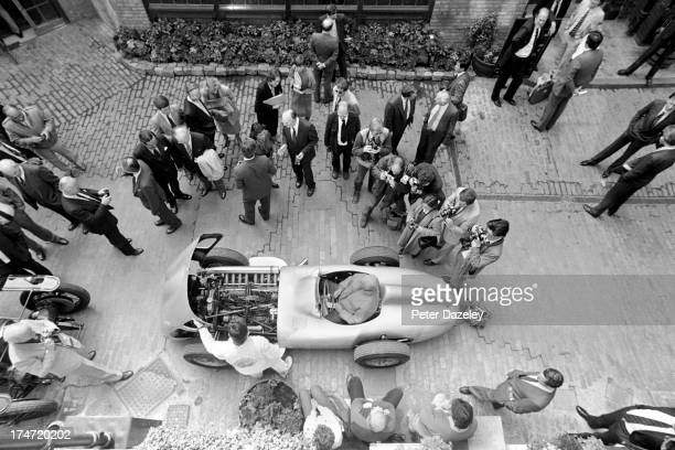 Argentinian racing car driver Juan Manuel Fangio poses for photographers in a 1954 MercedesBenz W196R at the Porter Tun Rooms Chiswell Street London...