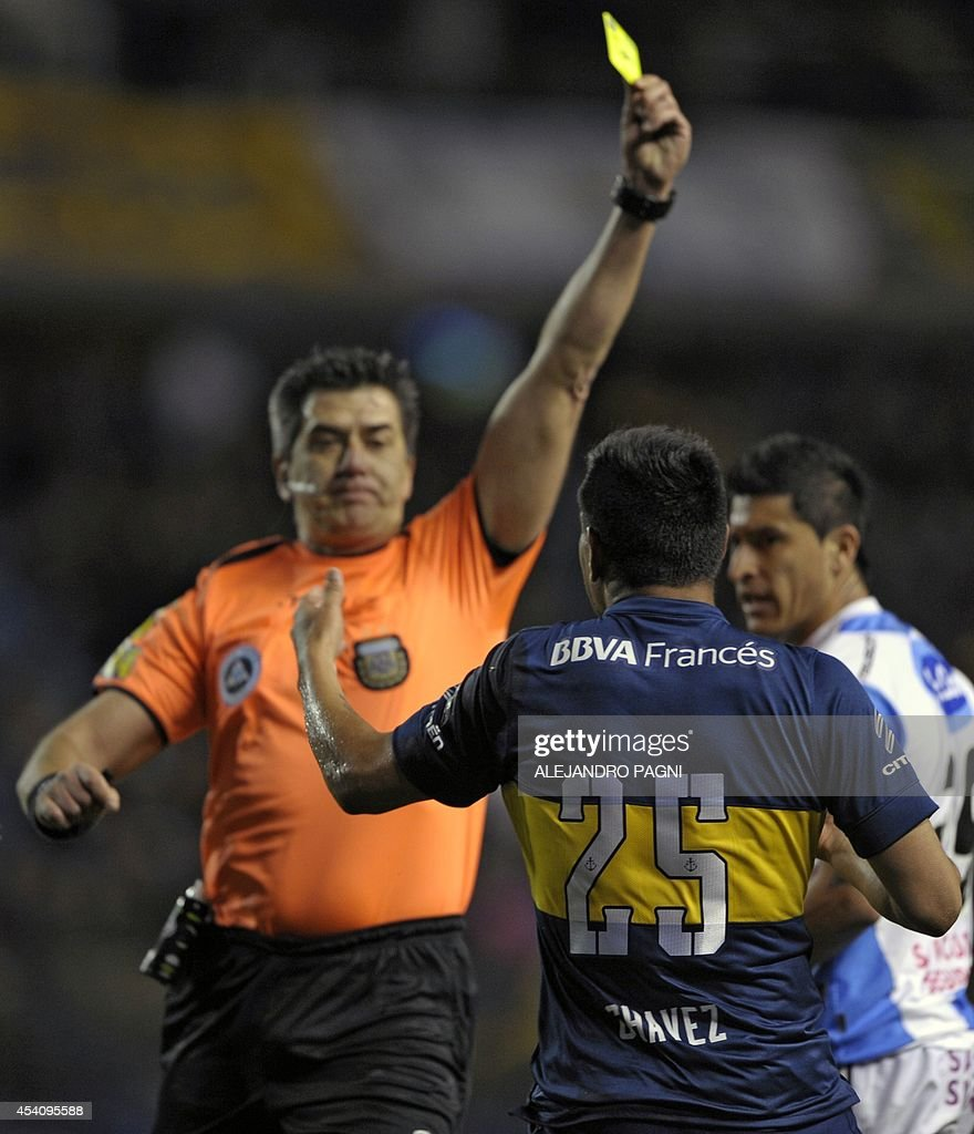 Argentinian referee Carlos Maglio (L) shows a yellow card to Boca Juniors' forward Andres Chavez (C) during their Argentine First Division football match against Atletico Rafaela, at the Bombonera stadium in Buenos Aires, Argentina, on August 24, 2014. AFP PHOTO / Alejandro PAGNI