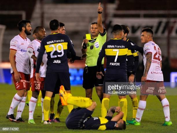 Argentinian referee Dario Herrera shows a yellow card to Boca Juniors' defender Leonardo Jara during their Argentina First Division football match...