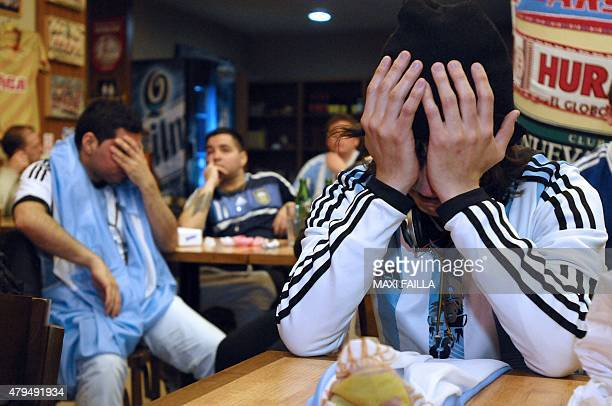 Argentinian supporters react in dejection after losing the 2015 Copa America final football match to Chile by penalty shootout in a restaurant in...