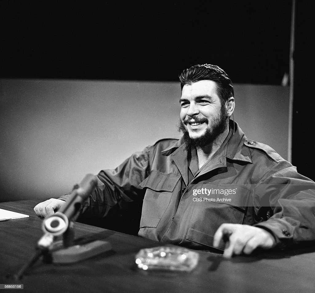 Argentinianborn Marxist revolutionary Ernesto Che Guevara Cuban Minister of Industry dressed in military fatigues smiles and smokes a cigar as he...