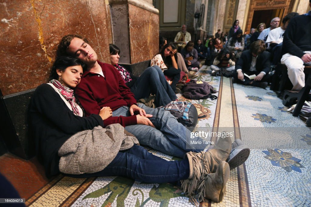 Argentinians rest in Metropolitan Cathedral during a vigil while waiting to watch a live broadcast of the installation of Pope Francis in Saint Peter's Square on March 19, 2013 in Buenos Aires, Argentina. Francis was the archbishop of Buenos Aires and is the first Pope to hail from Latin America. Celebrants watched in the early morning hours as the event was broadcast at 6:00 a.m. Buenos Aires time.