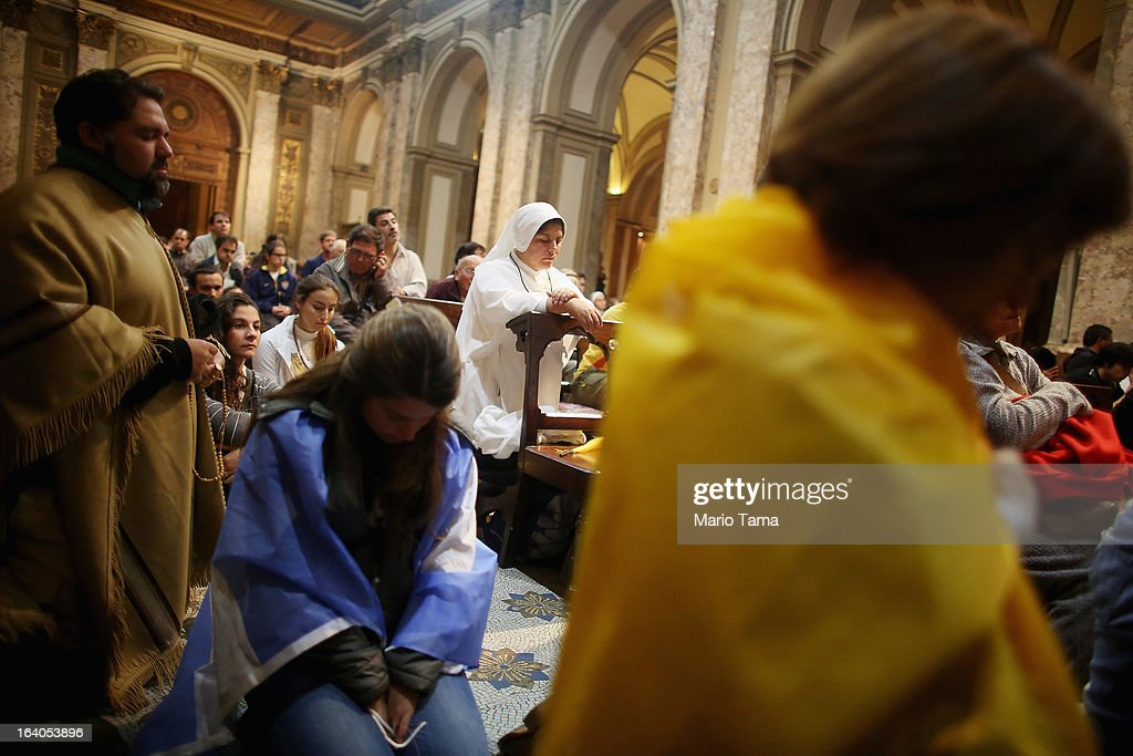 Argentinians sit in Metropolitan Cathedral during an overnight vigil while waiting to watch a live broadcast of the installation of Pope Francis in Saint Peter's Square on March 19, 2013 in Buenos Aires, Argentina. Francis was the archbishop of Buenos Aires and is the first Pope to hail from Latin America. Celebrants watched in the early morning hours as the event was broadcast at 6:00 a.m. Buenos Aires time.