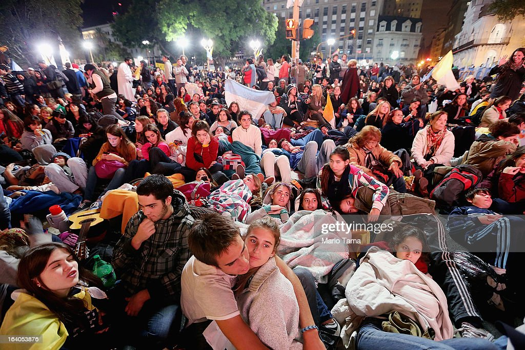 Argentinians sit in Plaza de Mayo during an overnight vigil while waiting to watch a live broadcast of the installation of Pope Francis in Saint Peter's Square on March 19, 2013 in Buenos Aires, Argentina. Francis was the archbishop of Buenos Aires and is the first Pope to hail from Latin America. Celebrants watched in the early morning hours as the event was broadcast at 6:00 a.m. Buenos Aires time.