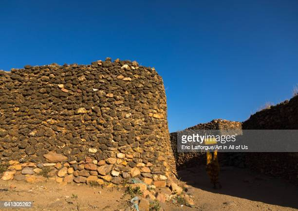 Argoba woman carrying water in jericans in a traditional stone houses clifftop village on January 12 2017 in Koremi Ethiopia