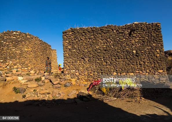 Argoba women carrying water in jericans in a traditional stone houses clifftop village on January 12 2017 in Koremi Ethiopia