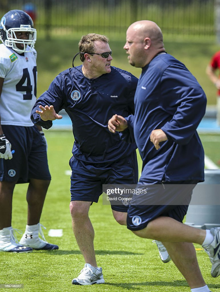 Argos Defensive Coordinator Chris Jones (centre) runs a drill with his players during the 2nd day of Argos rookie camp at St. Thomas Aquinas High School field.