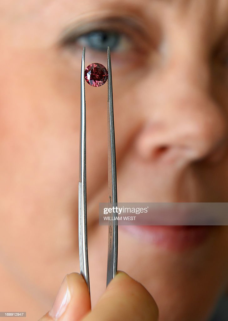 Argyle Pink Diamonds manager Josephine Johnson inspects the biggest 'red' diamond produced by mining giant Rio Tinto's Australian mine and which is up for sale, amid an 'explosion' in demand from Asia for the pink-hued stones, in Sydney on May 17, 2013. The Argyle Phoenix, a 1.56 carat round brillant gem, is one of three red diamonds on offer at the annual Argyle Pink Diamonds Tender -- the first time in the 30-year history of exclusive sales that it has included three red stones. AFP PHOTO / William WEST