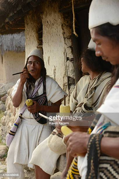 Arhuaco men hold Poporos while hanging around inside the walled village on January 23 2015 Nabusimake Colombia Poporo is a gourd containing lime...