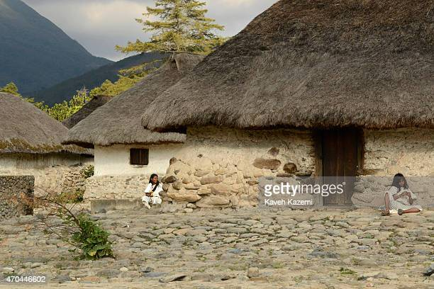 Arhuaco youth sit idly on the ground by the huts inside their walled village on January 23 2015 Nabusimake Colombia Nabusimake is the spiritual...