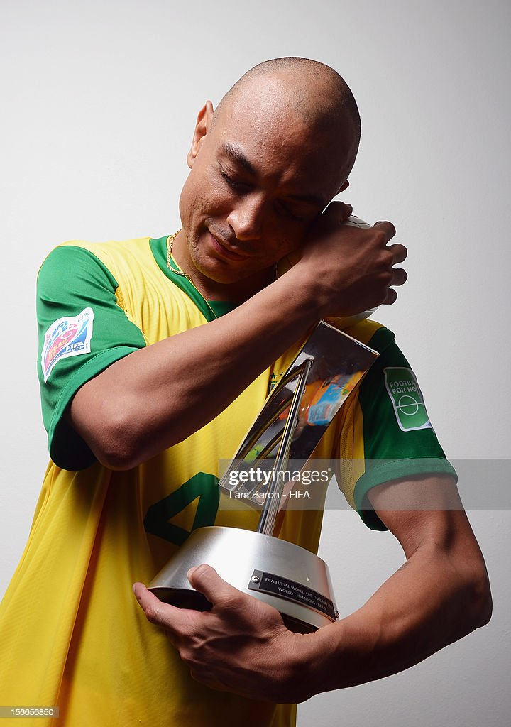 Ari of Brazil poses with the trophy in the locker room after winning the FIFA Futsal World Cup Final at Indoor Stadium Huamark on November 18 2012 in...