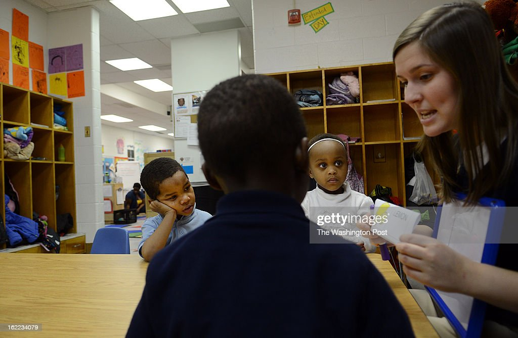 Aria Nickens, 4, second from right, Santonio Long, 4, left, and Destin Lewis, 3, center, listen to Rachel Hickman, right, lead teacher at AppleTree Early Learning Public Charter School who teaches them how to read and pronounce the letters of the alphabet during early morning lessons at the Apple Tree Early Learning Public Charter School in Southwest. President Obama proposed universal public preschool to raise the educational level; DC is already doing it. A look at how it's working out, visiting a class of preschoolers in DC.