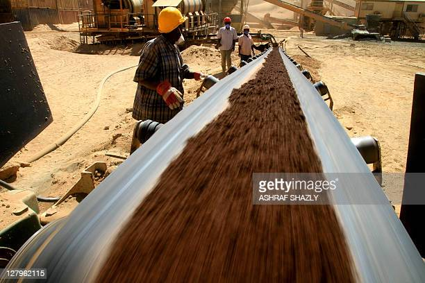 A Ariab worker watches a belt carrying earth at a gold mine in the Sudanese desert 800 kms northeast of the capital Khartoum on October 3 2011...