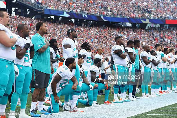 Arian Foster Kenny Stills and Michael Thomas of the Miami Dolphins kneel during the national anthem before the game against the New England Patriots...