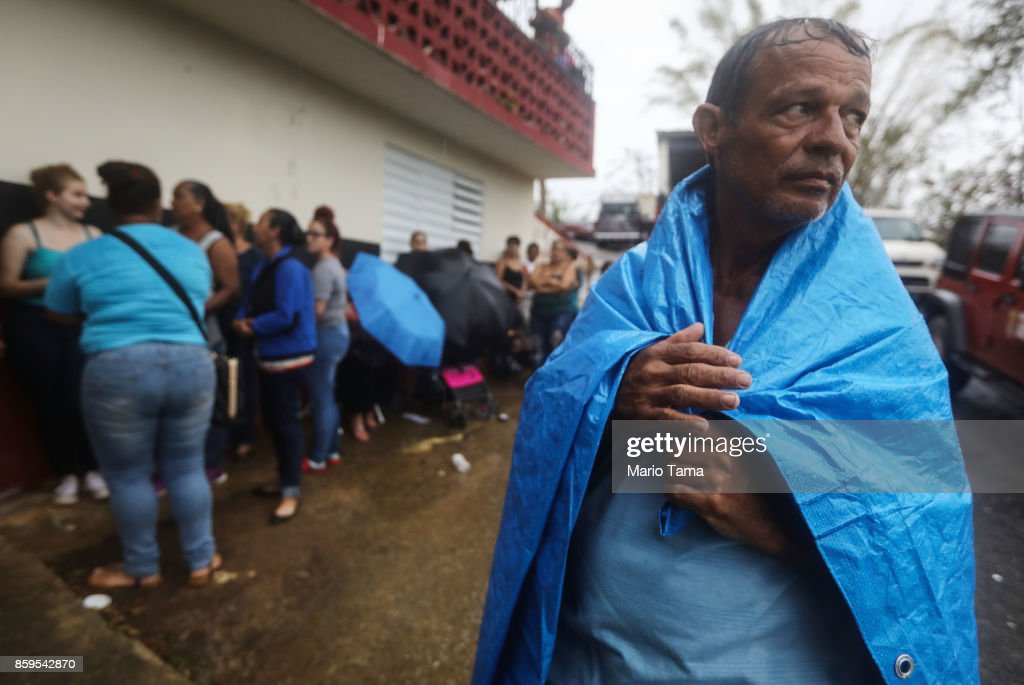 Arian Rodriguez covers himself with a tarp as residents wait in the rain to register with FEMA more than two weeks after Hurricane Maria hit the island, on October 9, 2017 in Jayuya, Puerto Rico. Residents said many had been waiting on line outside for more than seven hours. Most of the municipality is without water or power. Only 15 percent of Puerto Rico's grid electricity has been restored. Puerto Rico experienced widespread damage including most of the electrical, gas and water grid as well as agriculture after Hurricane Maria, a category 4 hurricane, swept through.