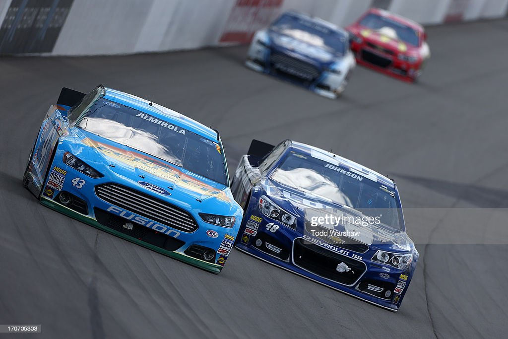 Aric Almirola, driver of the #43 Eckrich Ford, races Jimmie Johnson, driver of the #48 Lowe's Chevrolet, during the NASCAR Sprint Cup Series Quicken Loans 400 at Michigan International Speedway on June 16, 2013 in Brooklyn, Michigan.