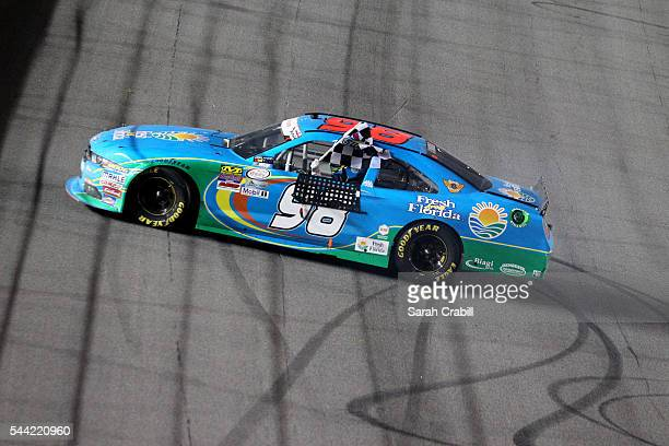 Aric Almirola driver of the Fresh From Florida Ford celebrates with the checkered flag after winning the NASCAR XFINITY Series Subway Firecracker 250...