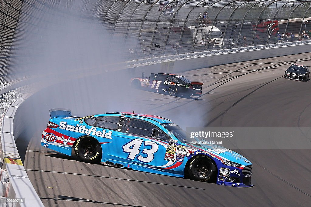 <a gi-track='captionPersonalityLinkClicked' href=/galleries/search?phrase=Aric+Almirola&family=editorial&specificpeople=574878 ng-click='$event.stopPropagation()'>Aric Almirola</a>, driver of the #43 Smithfield Ford, and <a gi-track='captionPersonalityLinkClicked' href=/galleries/search?phrase=Denny+Hamlin&family=editorial&specificpeople=504674 ng-click='$event.stopPropagation()'>Denny Hamlin</a>, driver of the #11 FedEx Express Toyota, slide on the track in an on-track incident during the NASCAR Sprint Cup Series Quicken Loans 400 at Michigan International Speedway on June 15, 2014 in Brooklyn, Michigan.