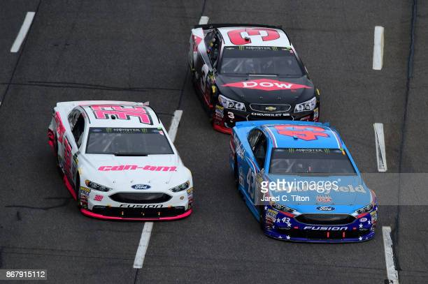 Aric Almirola driver of the Smithfield Ford leads Matt DiBenedetto driver of the Keen Parts Ford and Austin Dillon driver of the DOW Chevrolet during...