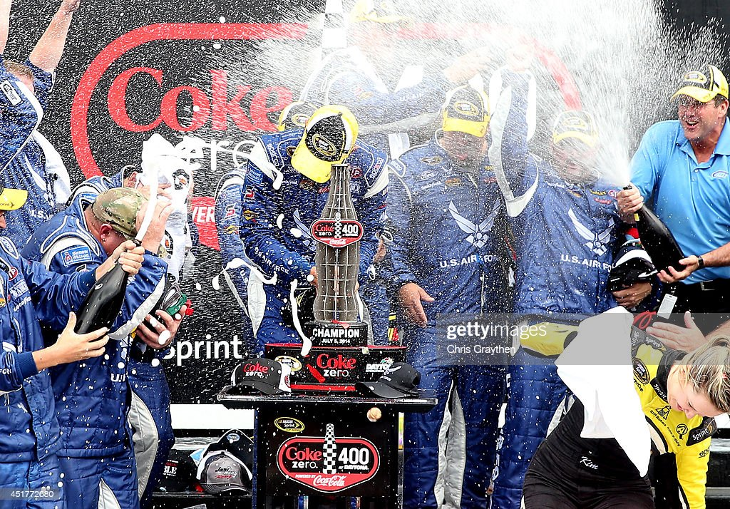Aric Almirola, driver of the #43 United States Air Force Ford, celebrates with champagne in Victory Lane after winning the NASCAR Sprint Cup Series Coke Zero 400 after the race was called for weather at Daytona International Speedway on July 6, 2014 in Daytona Beach, Florida.